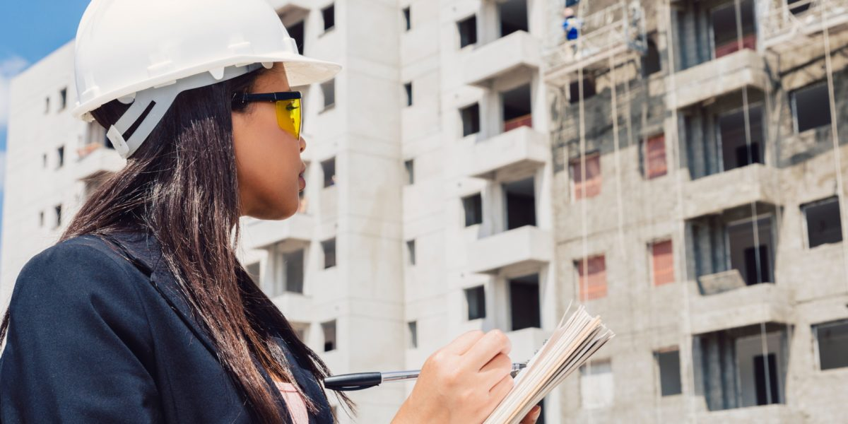 Dream Legacy Foundation - African-American woman in safety helmet writing on notepad near a building construction